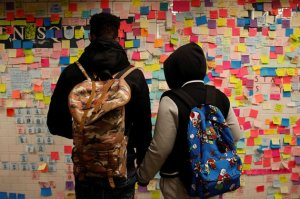 People holds hands looking at post-election Post-it notes  pasted along a tiled walk at Union Square subway station in New York
